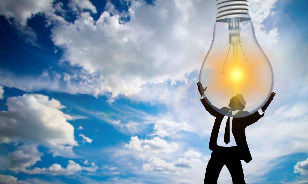 man holding big light bulb with sky and clouds background