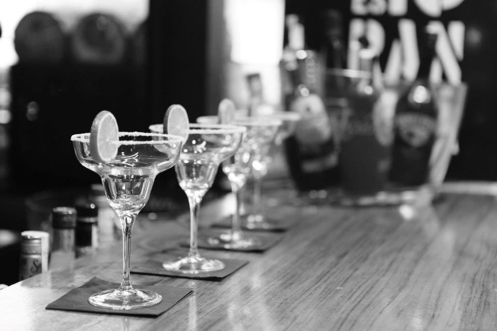 black and white image of drinking glasses at bar with bar insurance
