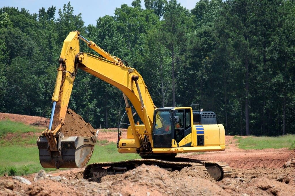 And excavator lifting sand with excavator insurance