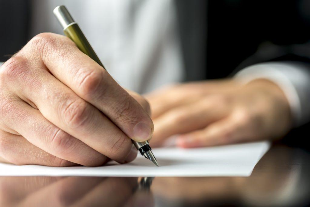 Gentleman signing insurance paper